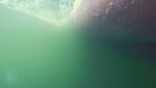 Underwater shot of bubbles passing by on the bottom of boat