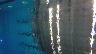 Underwater shot of man swimming breaststroke at pool