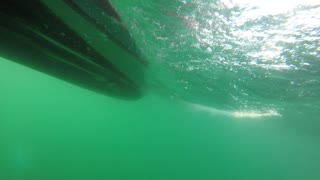 Underwater shot of small raft boat on rough ocean