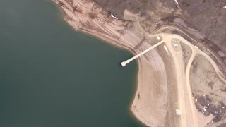 Very high rotating aerial shot of low mountain reservoir and dam