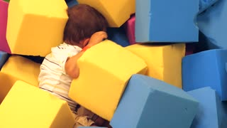A Boy Playing In A Soft Foam Pit In A Jump House