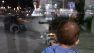 A Boy Watching Planes Taxi At The International Airport