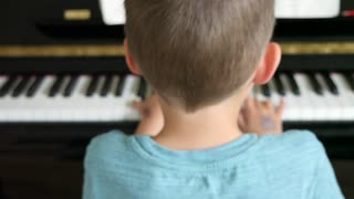 A Cute Boy Practices His Songs On A Black Piano