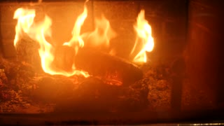A dolly shot of a roaring fire in a cozy fireplace in room