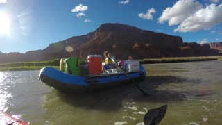 A Family In Kayaks And Tubes On The Colorado River Near Moab Utah