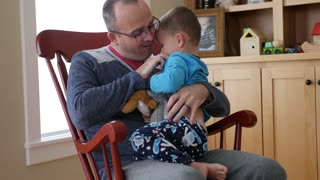 A Father Tickles His Toddler In A Rocking Chair In House