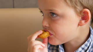 A Little Boy Eats Fast Food Chicken Nuggets And French Fries For Lunch