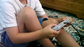 A Little Boy Playing With A Video Game Console