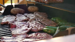 A Man Cooks Tasty Meat And Vegetables On A Barbeque Grill
