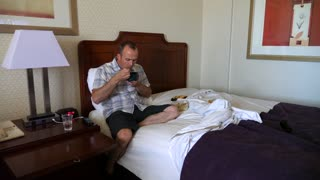 A Man Watches Television And Eats Lunch On Hotel Bed