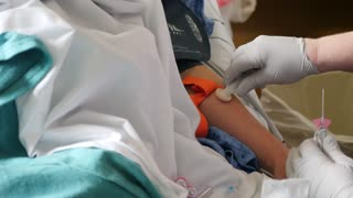 A Nurse Prepares To Put An Iv Into A Womans Arm At The Hospital