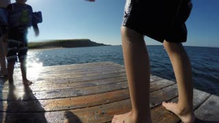 A Shot Of Boy Jumping From A Dock And Swimming In Ocean