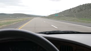 A Steering Wheel And Dashboard In A Car Driving Fast On A Highway