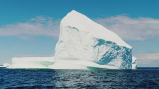 A Tall And Immense Ice Berg Floats Through Blue Arctic Water