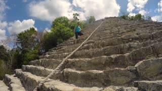 A Tourist Climbing Down Stairs On Large Mayan Ruins In Mexico