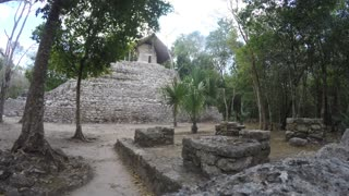 A Tourist Walks Through Large Mayan Ruins In Mexico