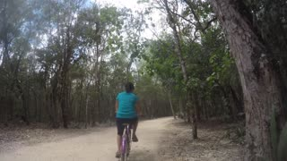 A Woman Riding A Bike By The Mayan Ruins In Mexico