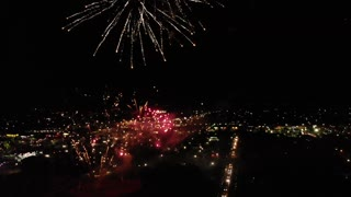Aerial Descending Shot Of A Large Crowd At Fireworks And Carnival