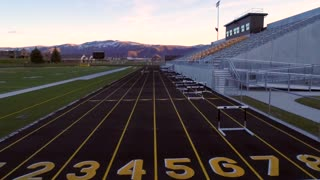 Aerial High Shot Of Track And Field At Sunset In Mountain Valley