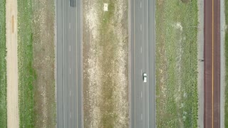 Aerial High Shot Of Vehicles Traveling Along A Highway In Spring