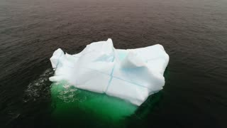 Aerial Moving Shot Of A Blue Iceberg Floating In Ocean