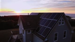 Aerial Of A Coastal Home With Solar Panels At Sunset