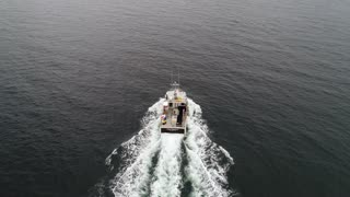 Aerial Of A Fishing Boat While Checking Their Lobster Traps In Ocean