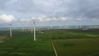 Aerial Of A Large Windmill Farm In Green Field With Clouds