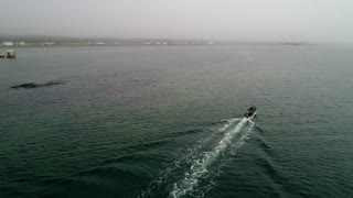 Aerial Of A Man In Small Fishing Boat Moving Through Fog On The Ocean