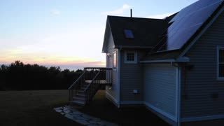 Aerial Of Coastal Home With Solar Panels At Sunset