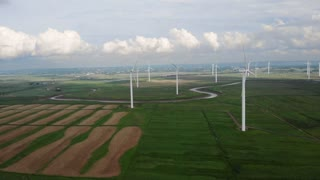 Aerial Of Large Windmill Farm In Green Field With Clouds