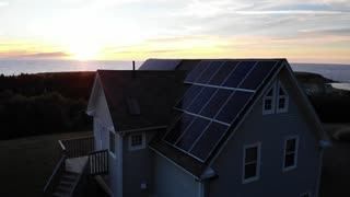 Aerial Of Solar Panels On Roof And Amazing Ocean Sunset