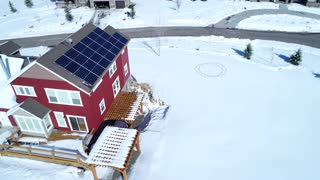Aerial Rotating Shot Of A House With Solar Panels In The Winter And People