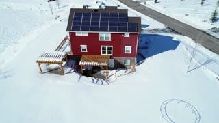 Aerial Rotating Shot Of A House With Solar Panels In The Winter