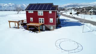 Aerial Rotating Shot Of House With Solar Panels In The Winter