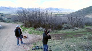 Aerial Shot As Men Shoot A 12 Guage Shotgun At A Clay Pigeons
