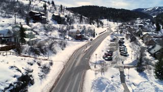 Aerial Shot Of Cars Driving In Winter Mountain Resort Town In Utah