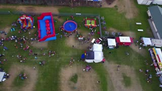 Aerial Shot Of Families At A Rural Fair With Rides