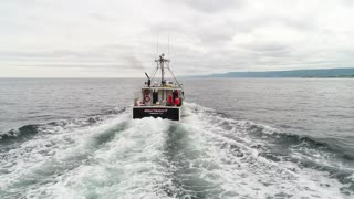 Aerial Shot Of Ocean Commercial Fishing Boat Fishing With Lobster Traps