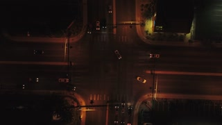 Aerial Shot Of Vehicles Driving On A Busy Road Through A City At Night