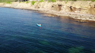 An Aerial Shot Of Family Riding In A Fun Kayak On An Ocean
