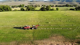 An Aerial Shot Of Farmer Collecting Hay Into Bales With A Tractor