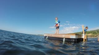 An Underwater Shot Of Boy Jumping From A Dock And Swimming In Ocean