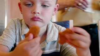 Boy Eating Chicken Nuggets And French Fries At Restaurant Table