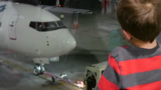 Boy Watching Planes Taxi At The International Airport