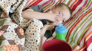 Cute Little Boy Liying Sick On The Couch With A Red Bowl To Throw Up