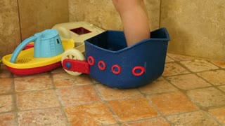Cute Toddlers Feet In A Shower With Toys As He Plays