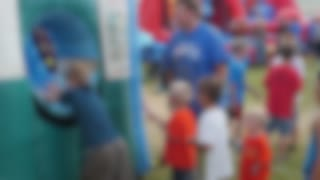 Families Play At A Rural Fair With Rides And Activities Blurred