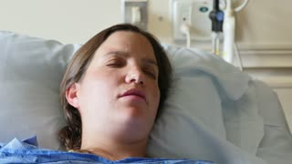 Handheld Shot Of Woman In Hospital Bed In Labor