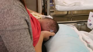 New Mother Nurses Her Newborn Girl At The Hospital
